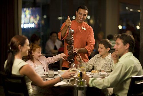 """<p>ポイント2 スタッフが長い串を持ってテーブルでサーブします。 焼きたての熱々お肉や魚介類が、""""食べ放題""""!</p>"""